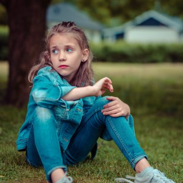 little girl sitting in grass