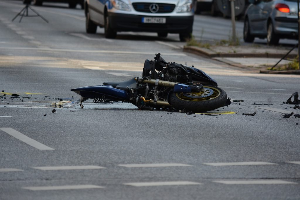 motorcycle on its side with broken pieces around following a crash