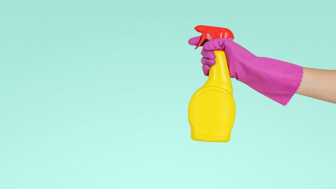 person holding yellow cleaning spray bottle