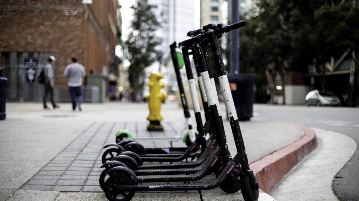 A line of electric scooters on a sidewalk