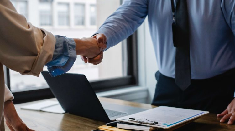 Two figures in professional attire shake hands as they work together to address a contract dispute